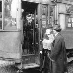 hombres con mascarilla subiendo a un tranvía